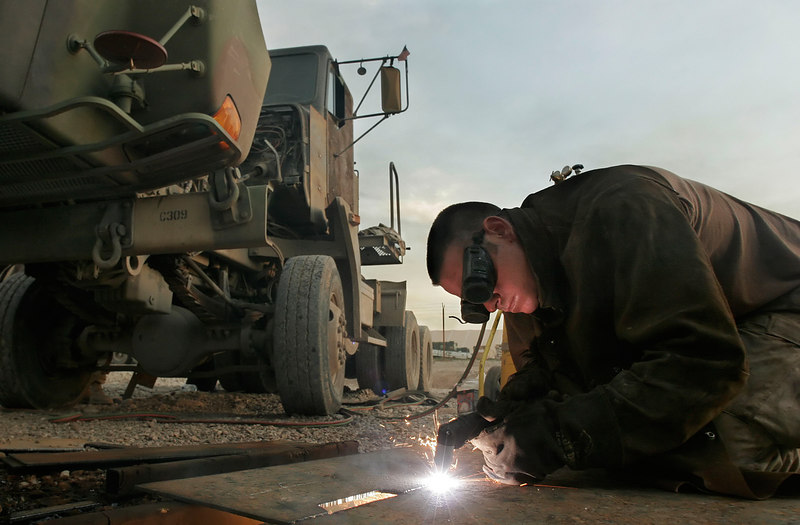 Using a plasma torch to up-iron a truck for protection against roadside bombs.