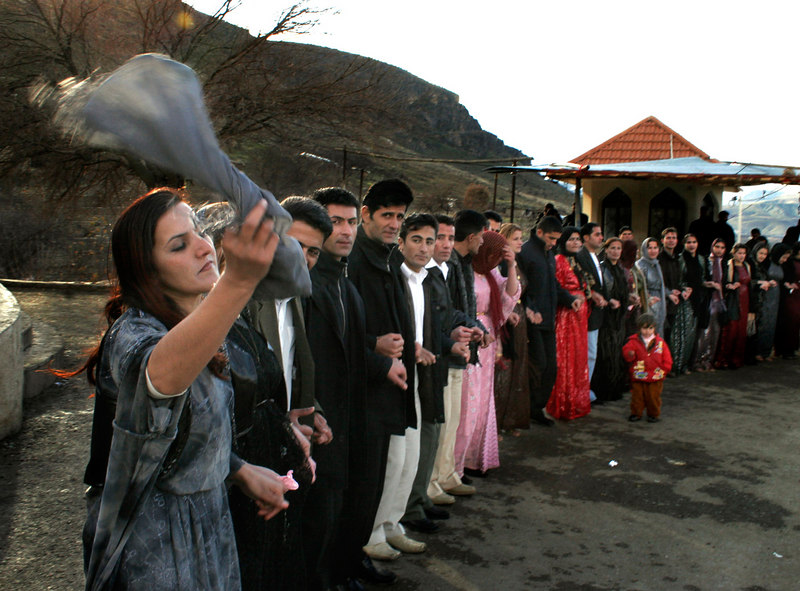Kurdish women and men participate in a traditional dance during a wedding in Irbil Province.