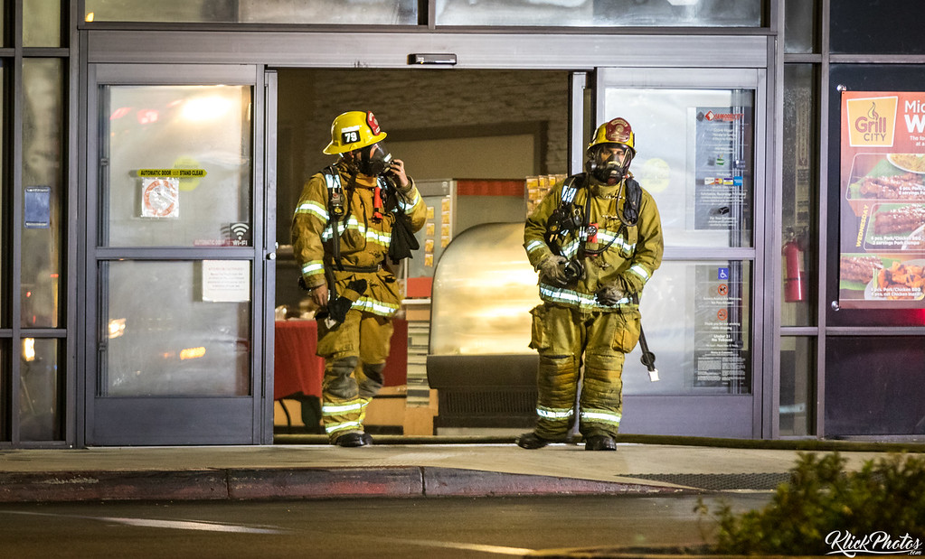 Firefighters emerge from the entrance of the Seafood City Supermarket in Irvine after a fire broke early Friday morning.