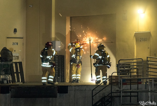 Firefighters force access using power tools at the rear entrance to the Seafood City Supermarket in Irvine after a fire broke out early Friday morning.