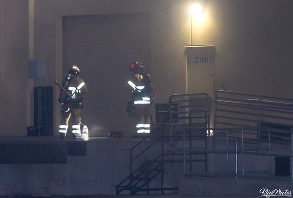 Firefighters encounter heavy smoke at the rear entrance to the Seafood City Supermarket in Irvine after a fire broke out early Friday morning.