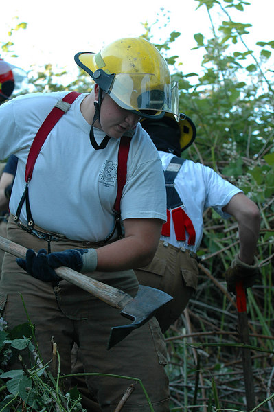 Yegor Bizyayev clears what's left of the blackberries to the dirt with his Pulaski Axe in creating the firebreak.