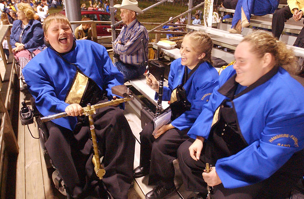 Jeremy Sohoski, 16, who has Duchenne muscular dystrophy, left, laughs as he and close friends and bandmates, Brittany Brode, 15, center, and Marcie Broussard, 15, goof around between playing during a Friday night football game in October.<br /> PHOTO/SCOTT ESLINGER                   OCT 15, 2004        <br /> 1015_Jeremy251.jpg