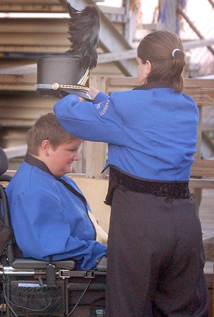Hamshire-Fannett High School trombone player Christy Thomas, 17, right, helps percussionist Jeremy Sohoski, 16, of Fannett,who  has Duchenne muscular dystrophy, with his hat as the marching band gets ready to perform before an football game in October.<br /> PHOTO/SCOTT ESLINGER                   OCT 15, 2004