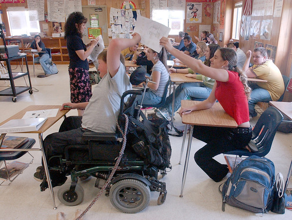 Jeremy Sohoski, 16, of Fannett, who has Duchenne muscular dystrophy, passes a quiz back to classmate, Rachel Broussard, 14, during Spanish class.<br /> PHOTO/SCOTT ESLINGER                   OCT 19, 2004<br /> 1019_Jeremy244.jpg