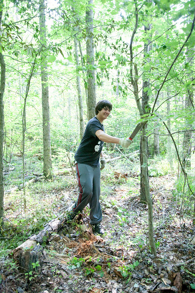 Andrew Barbera (age 14) uses a machete to clear underbrush.