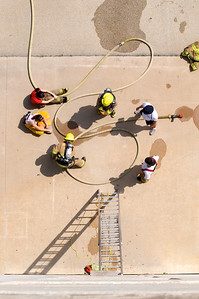 Students from the LBJ High School Fire Academy take part in a drill at the Austin Fire Department's training facility.