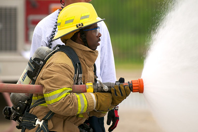 A participant in the LBJ High School Fire Academy practices using a fire hose during a drill.