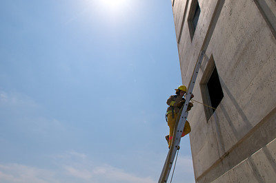 A student in the LBJ High School Fire Academy runs through a drill during a training day at the Austin Fire Department's training facility.