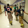 Three students in the LBJ High School Fire Academy walk through the halls on their way to visit a class and to recruit for next year's program.