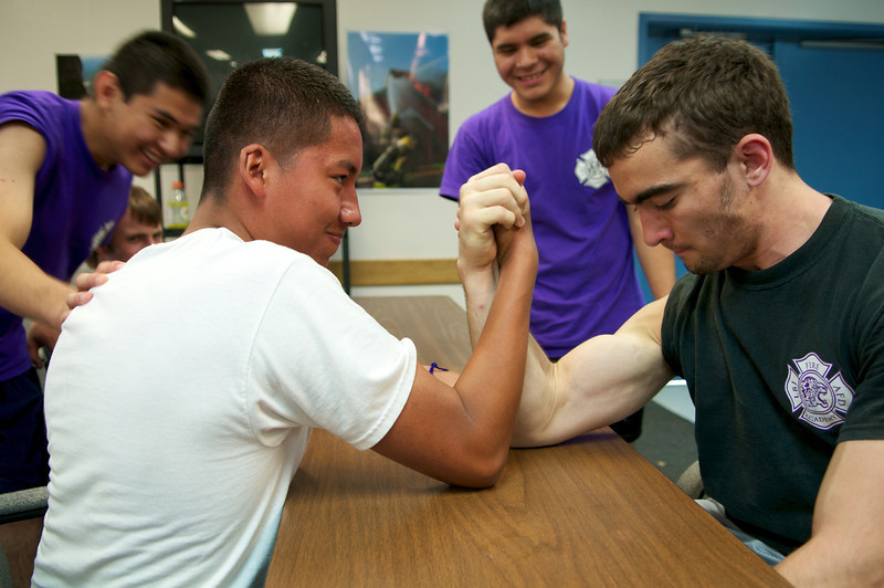 A junior in the LBJ High School Fire Academy arm wrestles a senior participant in the program during their lunch break on a training day at the Austin Fire Department's training facility.