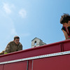 Two participants help organize the hoses on top of a fire truck used during a training exercise for the LBJ High School Fire Academy.