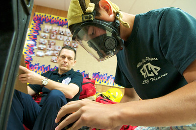 A student completes a skills assessment task as an instructor looks on during their class time at the LBJ High School Fire Academy.