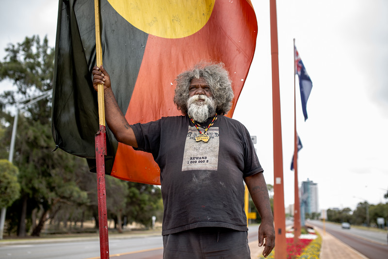 "Herbert Bropho stands with his back to the Australian Flags on the causeway outside the Matagarup First Nations Refugee Camp on Heirisson Island. He sustains substancial racial abuse from some cars as they drive by. He yells back ""I love you""."