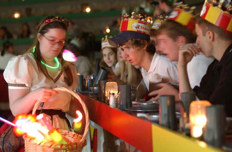 A wench hands out glow stick and other articles for cheering to some high school students in the crowd at Medieval times. Maximilian Franz/The Daily Record