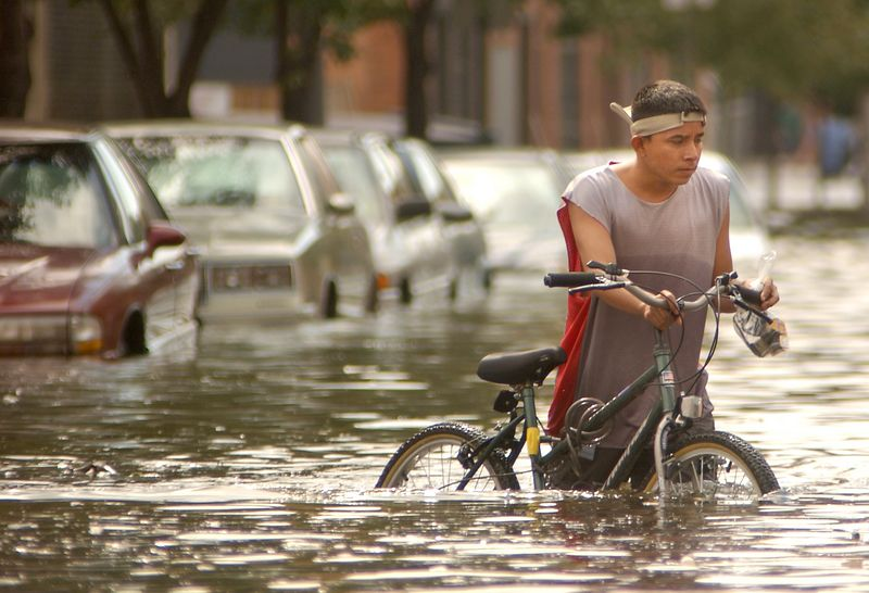 A boy walks his bike in the water of the Fells point flood, which rose above the intersection of Aliceanna and S. Wolf Street aver the swells of Huricane Isabel passed by Baltimore last night. Maximilian Franz/The Daily Record  9/19/03.