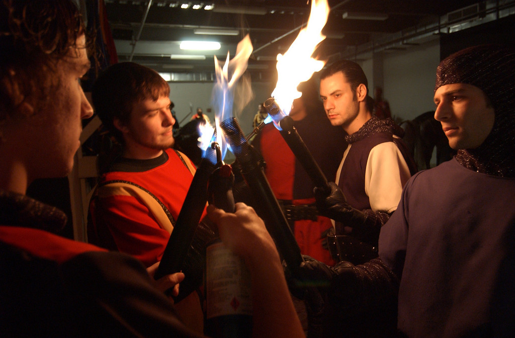 Squires lighting thier tourches before the grand entrance of the Knights for the lunch performace at Medieval Times in Arundel Mills Mall. Maximilian Franz/The Daily Record