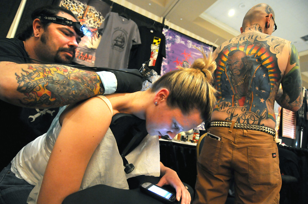04.08.11  BALTIMORE, MD- Tattoo artist, Dwaine Shannon of Saints And Sinners in Fells point inks a floral back piece on Baltimore Resident Bonnie Mimmack at the Baltimore Tattoo Arts Convention at the Sheraton Baltimore City Center Hotel on Friday April 8th. Shop worker Shawn Sapp stands in the background showing off a back piece that Dwaine did for him last year that won the Back Piece category of the annual competition at the convention. The event runs until Sunday April 10th. (The Daily Record/Maximilian Franz)