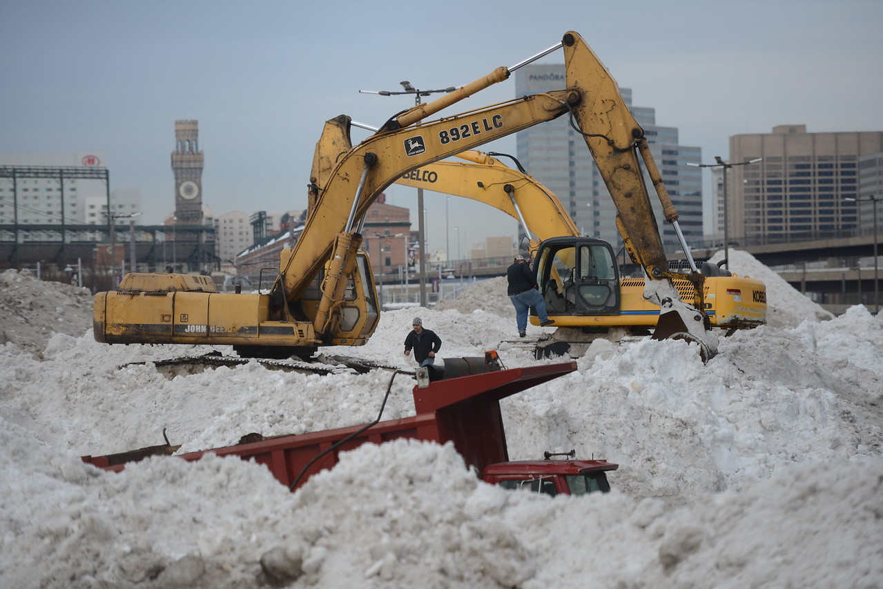 1.25.2016 BALTIMORE, MD- Snow removal Crews build massive piles of snow removed from Baltimore City streets and hauled to a parking lot under Interstate 395 by West Ostend Street near M&T Bank Stadium after a severe winter storm dumped nearly 40 inches of snow on Central Maryland. (The Daily Record/Maximilian Franz)