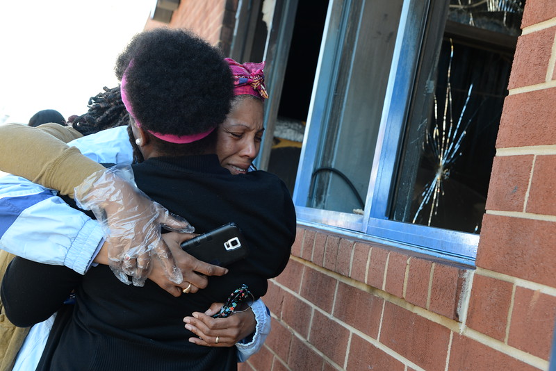 04.28.15 BALTIMORE, MD- Monica Bland, a worker for the CVS store at the intersection of Pennsylvania and North Avenue, that was the scene of a standoff between Police and rioters yesterday, is seen here consoled by her friends Erica Louis and Sara Wolfe after breaking into tears after seeing the destruction the morning after the looters had set fire to the structure. (The Daily Record/Maximilian Franz)