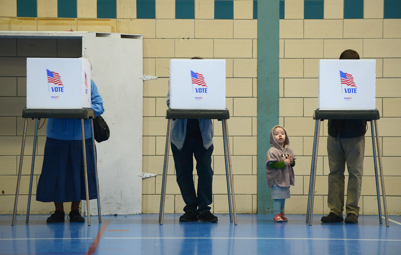 11.8.2016 BALTIMORE, MD- Isla Huggins, 2 1/2, waits while her parents, Sara Klemm and Alex Huggins, fill out their ballots at the Roosevelt Recreation Center in Hampden. (The Daily Record/Maximilian Franz)