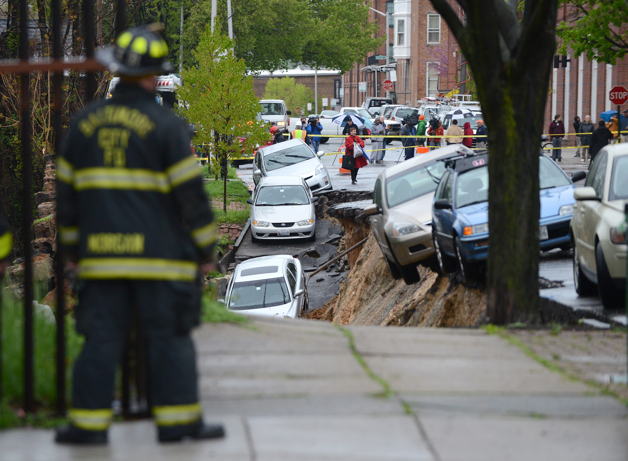4.30.14  BALTIMORE, MD- Heavy rain fell on Baltimore, causing a lot of problems, including a street collapse that sent soil, cars and debris into the CSX tracks along 26th Street between Charles and St. Paul Streets. (The Daily Record/Maximilian Franz)