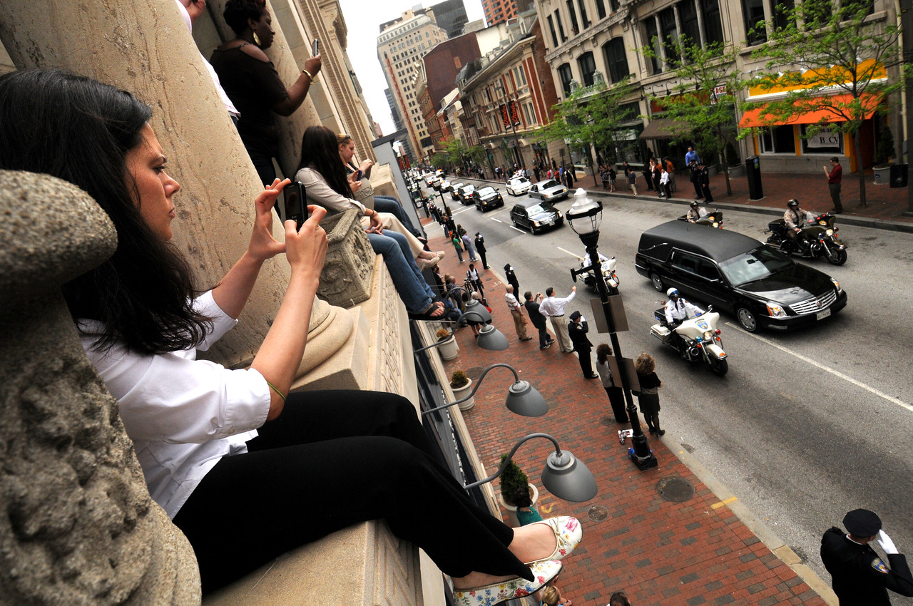 04.27.2011 BALTIMORE, MD-  Cheryl Miller, and fellow co-workers from Mering and Schlitz at 343 N. Charles Street sit on the 2nd floor balcony of their building to watch the Funeral Procession for William Donald Schaefer leave St. Pauls Church and drive him to his final resting place. Photos taken on Charles Street outside of St. Pauls Church at the end of the Funeral Service for William Donald Schaefer. (The Daily Record/Maximilian Franz).