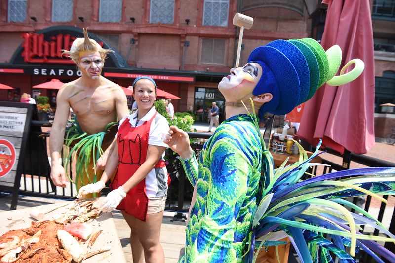 07.07.15 BALTIMORE, MD. Ten years after Cirque du Soleil Varekai debuted in Baltimore under the Big Top, it's back from Wednesday, July 8 to Sunday, July 12 at the Royal Farms Arena. As part of the promotion of the show returning to Baltimore, a few of the shows performers invaded Phillips Crab deck at the Baltimore Harbor. From left, Skywatcher character and Sarah Wong, Server at Phillips crab deck, watch Magioso character balance a crab hammer on his nose.  (The Daily Record/Maximilian Franz)