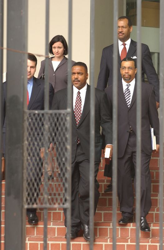 Nathan Chapman and his law team seen through the bars of the Security gate outside of the Federal coruthouse in Baltimore after he was convicted on 24 of the 32 charges against him. Maximilian Franz/The Daily Record  8/12/04.