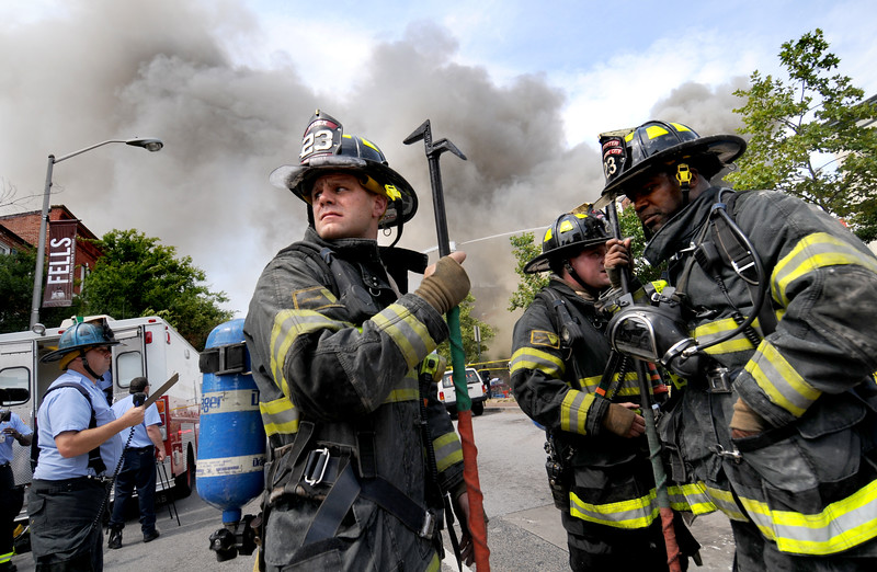 06.11.12- BALTIMORE, MD- Fire fighters from Truck 23 stand along Broadway street waiting for their commands while a vacant warehouse at South Broadway and Eastern Avenue burns in the background. The Fire Department said the buildings roof collapsed and one firefighter suffered a minor injury. Maximilian Franz