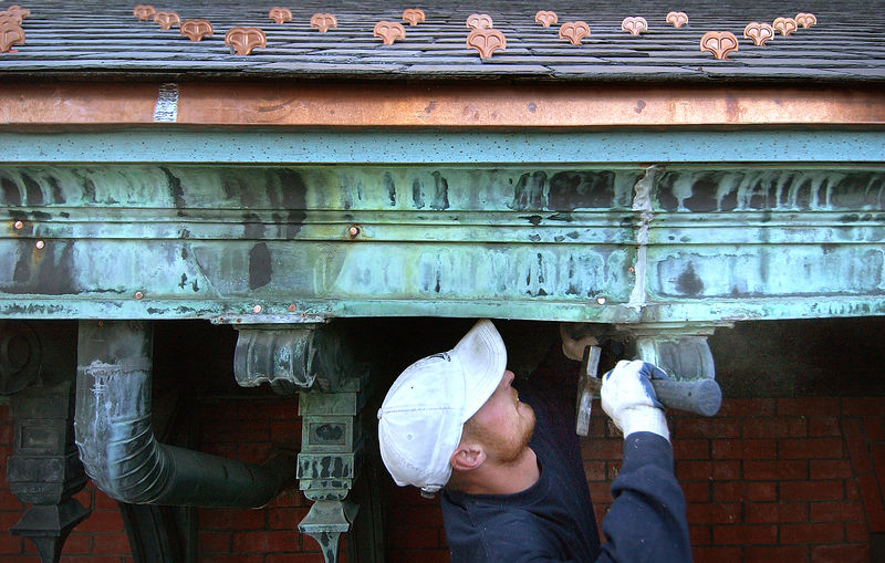 Roofing worker Uses new copper nails to reinforce the original rain gutters on the Marburg Building at Johns Hopkins Hospital. You can see the new snow guards on the slate roof above him. Maximilian Franz/The Daily Record  5/9/05.