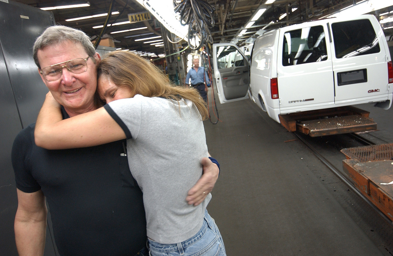 GM Replacement operator Heather Greene, 13 years huggs Gate Repairman Bob Farlow, 37years as the last Mini van passes by on the line at GM's Broening Highway plant. Maximilian Franz/The Daily Record  5/12/05.