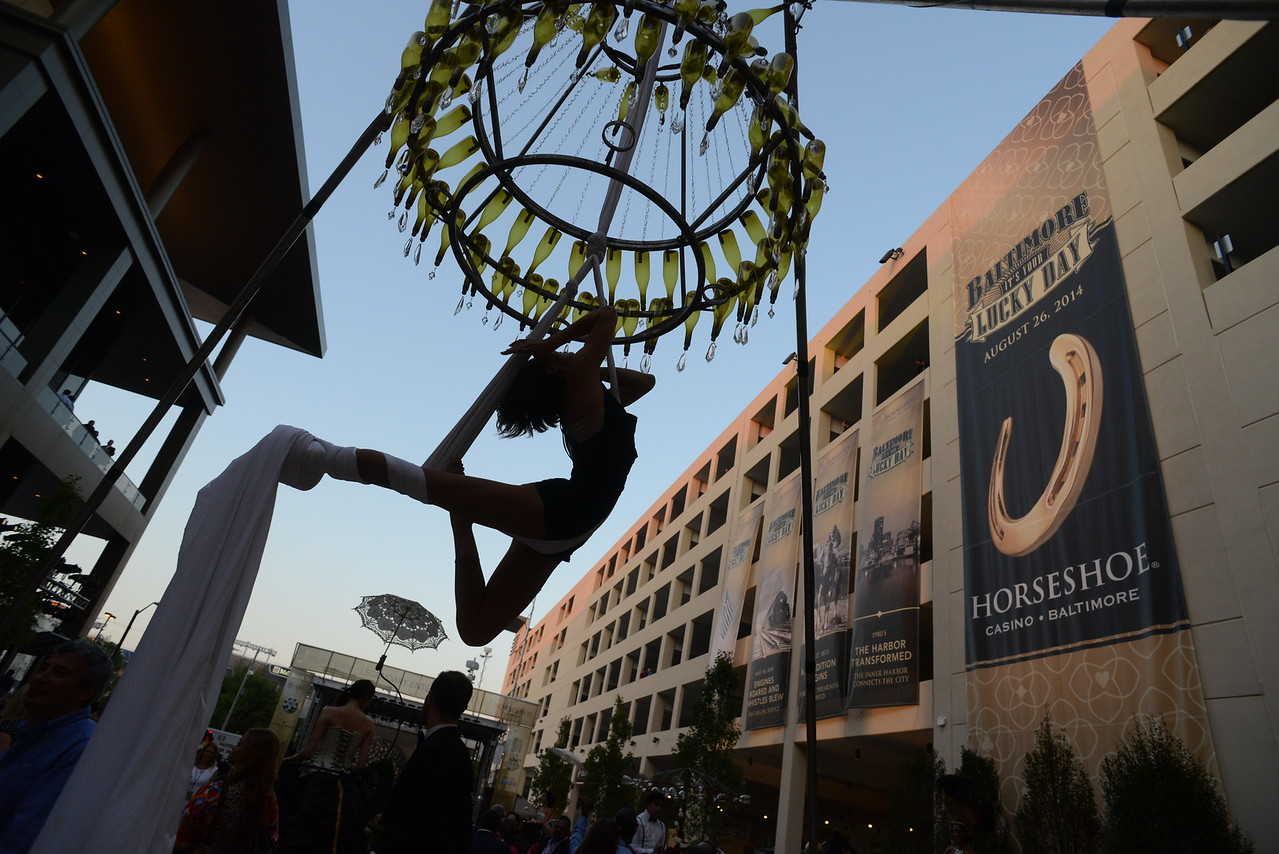 8.26.2014 BALTIMORE, MD- A performance artist swings from a chandler at the opening celebration of the Horseshoe Casino in Baltimore. (The Daily Record/Maximilian Franz)