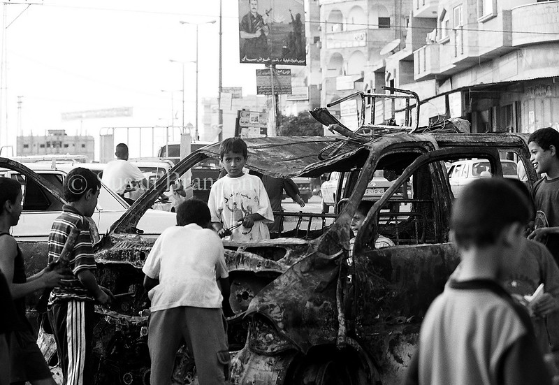Gazan children playing with a bombed car in Gaza City.