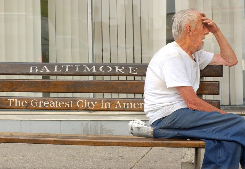 An old man sits on a bus stop bench on Eastern Avenue in Baltimore City portraying a stark contrast to the mayors new slogan for the city. 2005 Maximilian Franz/The Daily Record