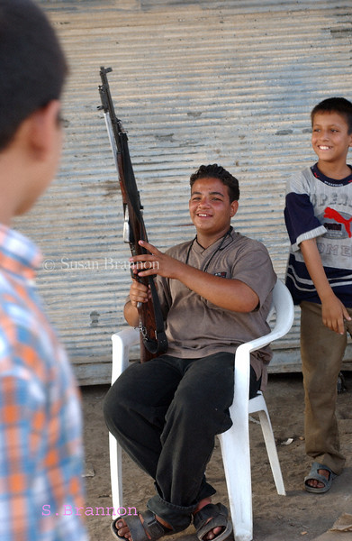 A young boy flaunting his gun to other boys just outside of the Baghdad Sunni Shrine.