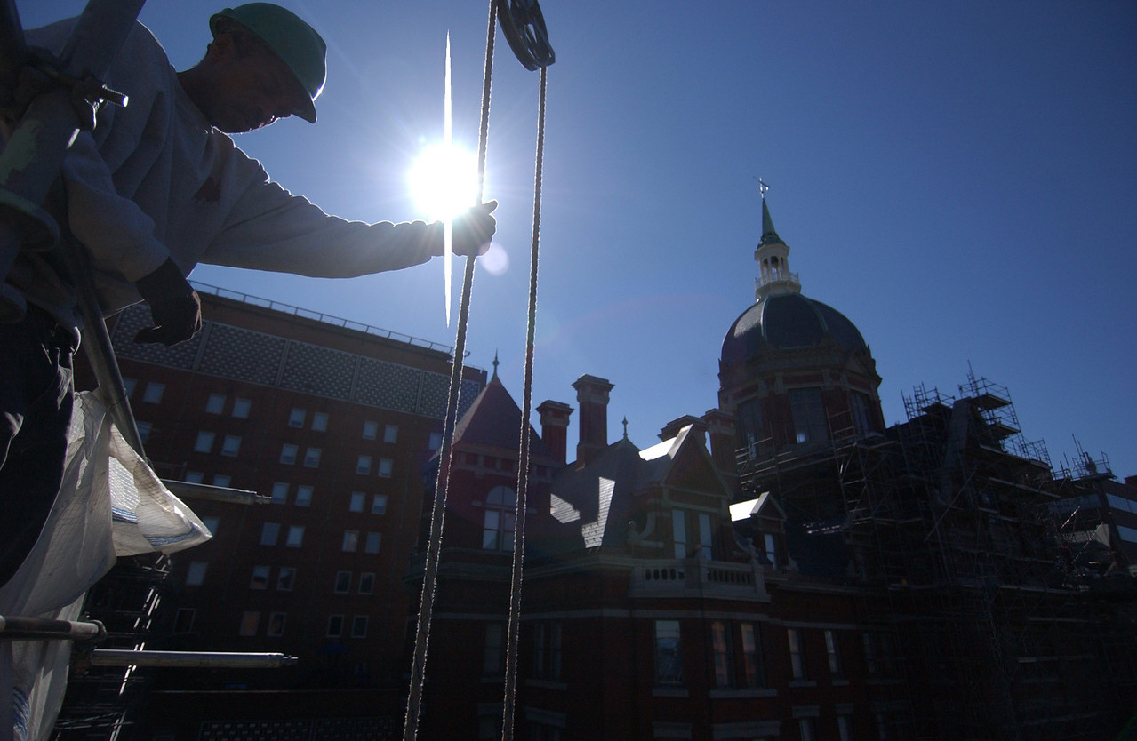 Construction worker Myco Holland lowering a bucket from the roof of the Marburg Building at Johns Hopkins Hospital. Maximilian Franz/The Daily Record 5/9/05.