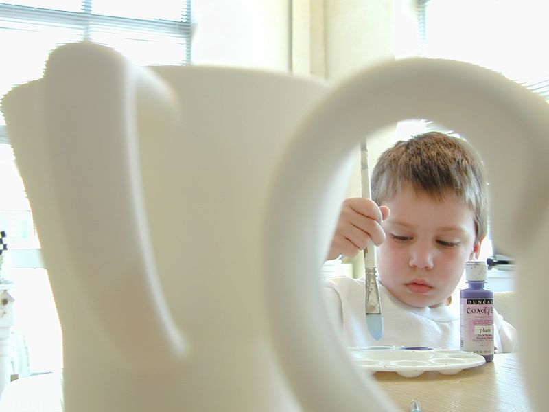 Five year old Casey Roemer paints a ceramic mug for his fathers birhday at Amazing Glaze in Mount Washington. Here he is seen through a handle of a mug that has not yet been painted. Maximilian Franz/The Daily Record  4/16/01.
