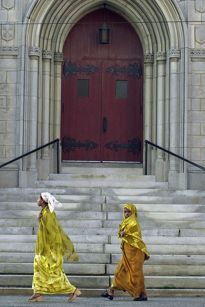 Young Somali girls pass by the entrance to an old Catholic church in Lewiston.