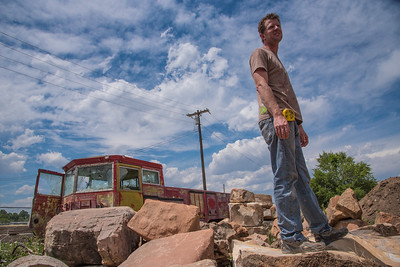 Ben Mozer, owner of the Lyric Cinema Cafe, stands on top of a boulder to be used in the landscaping of the new theater, located at 1209 N. College Ave., on Wednesday, June 28, 2017.  Mozer will convert the railroad car, parked behind him, into an outdoor projection booth for bike-in movie screenings.  The new 10,000 square foot building is tentatively scheduled to open in September.