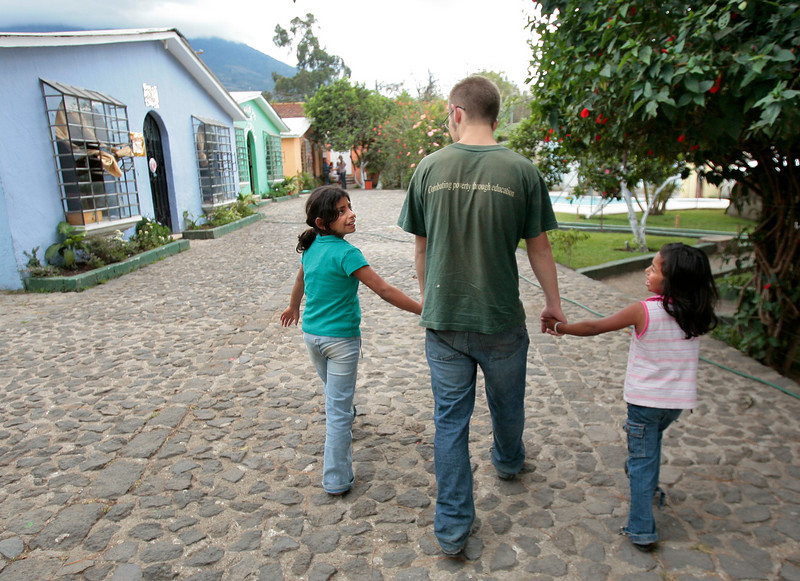 Sam Wilcox of Cumberland walks with Lupe Garcia Barrios, 11, left, and Catherine Lopez Reyes on the grounds of Casa Hogar in Antigua, Guatemala on Thursday, January 25, 2006. Wilcox has been volunteering with Safe Passage for five months and at Casa Hogar, a residential program, he works with children who have been severely neglected or abused.
