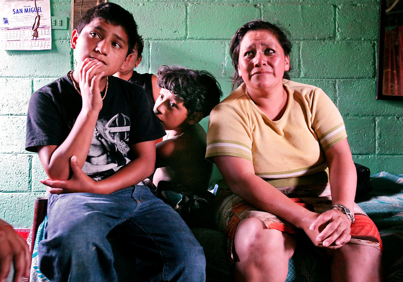 In their home near the Guatemala City garbage dump on Wednesday, January 24, 2007, Ruth Murcia is overcome with emotion while recalling memories of Hanley Denning, who helped her and seven of her ten children, including Santos Murcia, left and her adopted son Oscar Moises, with the Safe Passage program she founded. Murcier works in dump, earning between $4 and $6 per day for items she finds that have resale value.