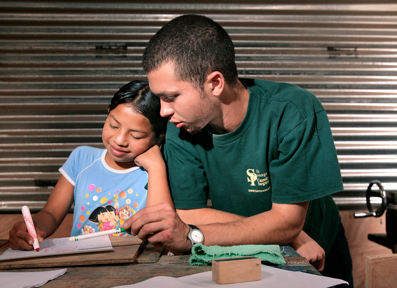 Bret Tonelli of Portland talks with Cindy Lopez Reyes, 10, while she works on a drawing on Thursday, January 25, 2006 for an art/woodworking class that Tonelli teaches at Casa Hogar in Antigua, Guatemala. Tonelli has been volunteering with Safe Passage for seven months and plans to stay for a year or possibly longer.