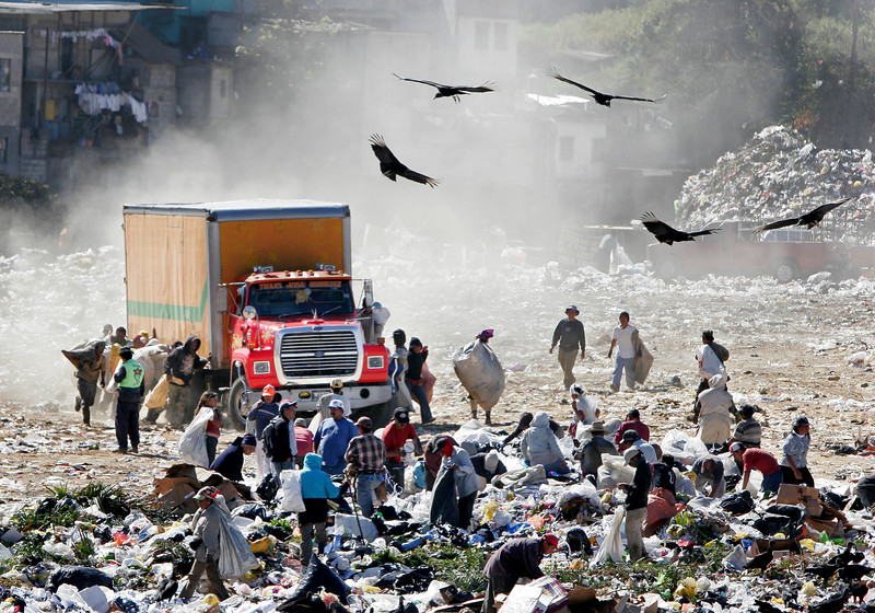 Guajeros, people who scavenge through the dump looking for items to resell, run alongside an arriving dump truck in the Guatemala City dump on Wednesday, January 24, 2007. By running alongside and holding on to a truck as it comes in, guajeros make an inherent claim over other scavengers for the right to pick through items that that truck dumps. In this process, though, some workers have been run over by the trucks.