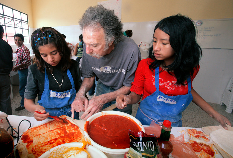 Stu Silverstein of Waterville teaches Evelyn Herrera, 14,  left, and Estafani Jimenez, 12, how to make pizza at the vocational program of Safe Passage in Guatemala City, Guatemala on Thursday, January 25, 2006. Silverstein came down to Safe Passage with a mid-coast Maine group called Masons on a Mission to build the wood-fired ovens for the program and returned with the group this year to teach students in the program how to use the ovens.