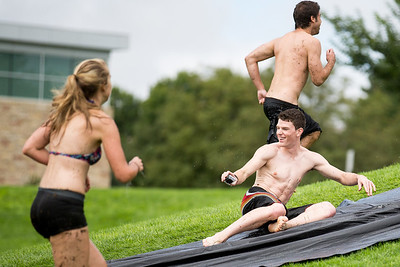 Austin McElderry, bottom right, slides down a slip n' slide made from a tarp on campus Friday afternoon after the relentelss downpoar of rain over the past few days.