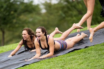 Maddie Scharlemann, middle, takes a ride on a slip n' slide students made on campus after the relentless rain over the past few days.