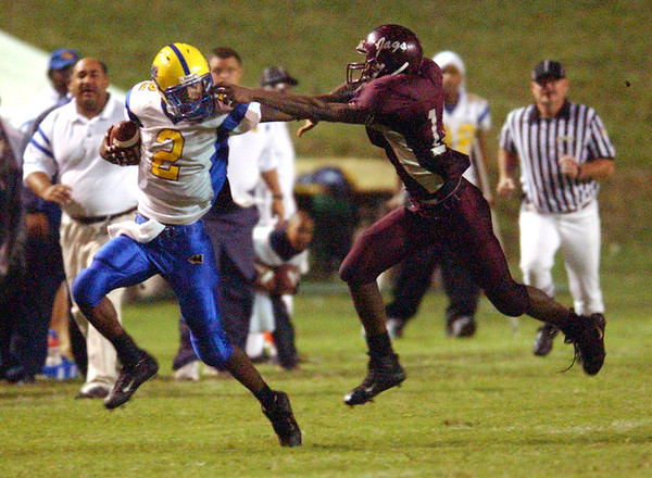 Central High School's Travis Oville (20), right, tries to get a hold of Ozen high School's Wallace Franklin Jr. (2), left, Friday night, Oct 8, 2004, at Cardinal Stadium.<br /> PHOTO/SCOTT ESLINGER           OCT 8, 2004