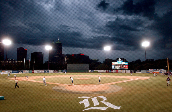 Storm clouds and the skyline of the Medical Center in Houston are lit up by lightning Friday night at Reckling Park as the grounds crew readys the field for the last two outs of the Texas Southern University-Rice  baseball game during the NCAA reegional tournament at Rice University.<br /> PHOTO/SCOTT ESLINGER        JUNE 4, 2004