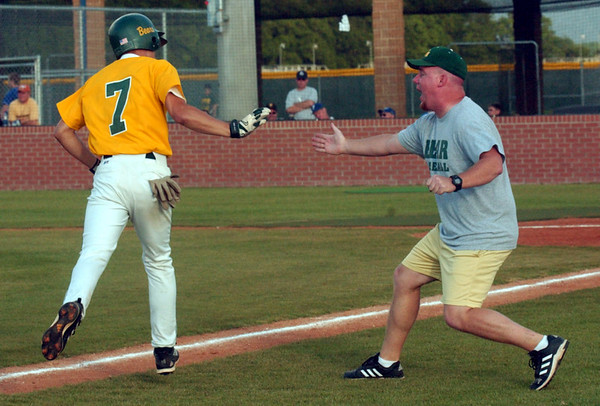 Little Cypress-Mauriceville High School trainer David Shaw, right, rushes to congratulate LC-M shortstop Shon Landry (7) as he heads toward home after hitting a two-run homer on a 3-1 pitch in his first at bat during the top of the first inning Thursday evening at Barbers Hill High School. Landry hit a single run homer on his next at bat in the second inning of the game which is the first of three in the Class 4A regional semi-finals.<br /> PHOTO/SCOTT ESLINGER       MAY 27, 2004